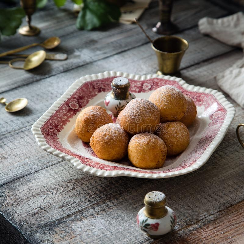Homemade small round ball donuts sprinkled with powdered sugar on vintage plate. With pink ornament on grey wooden table with vintage powder shakers, towel stock images