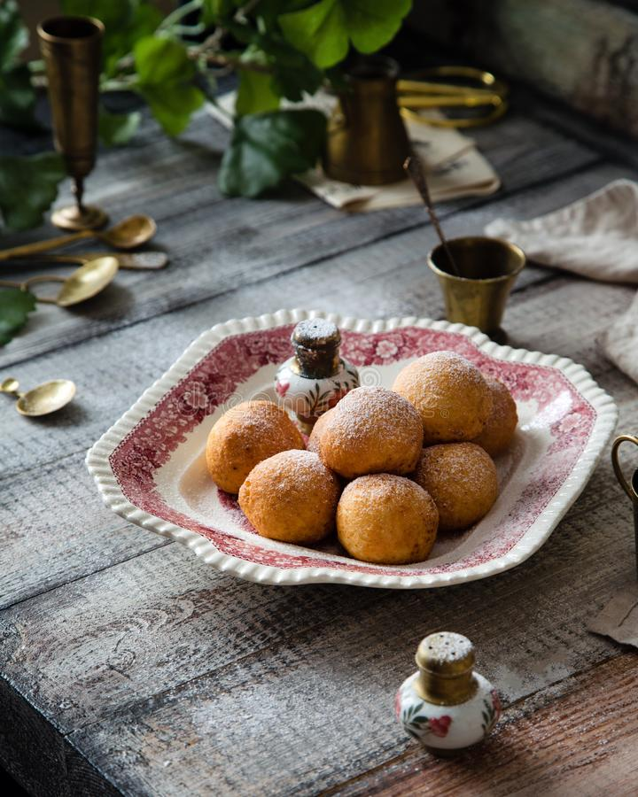 Homemade small round ball donuts sprinkled with powdered sugar on vintage plate. With pink ornament on grey wooden table with vintage powder shakers, towel stock photos