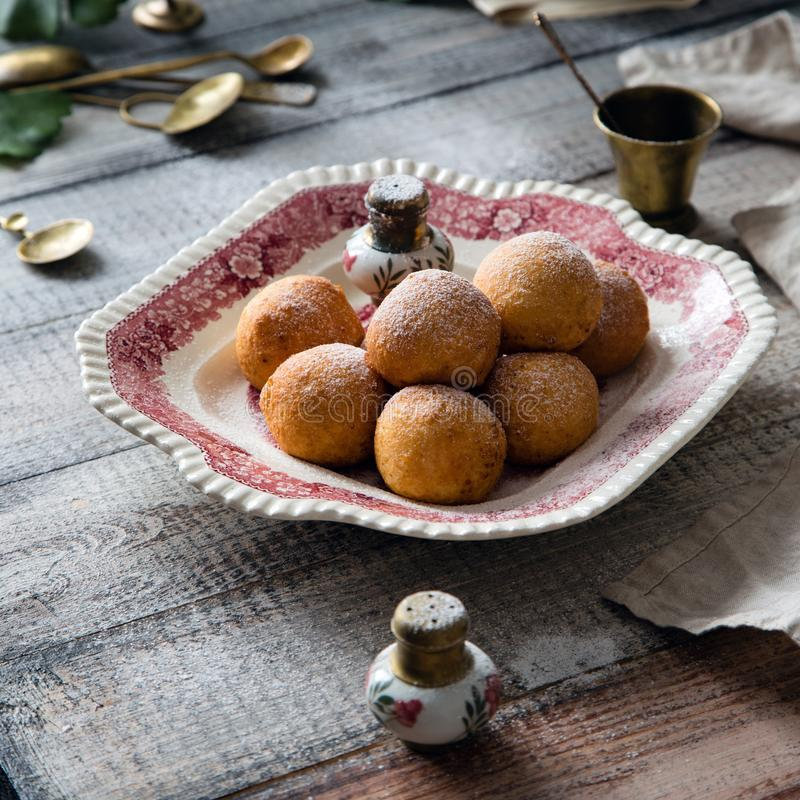 Homemade small round ball donuts sprinkled with powdered sugar on vintage plate. With pink ornament on grey wooden table with vintage powder shakers, towel royalty free stock images