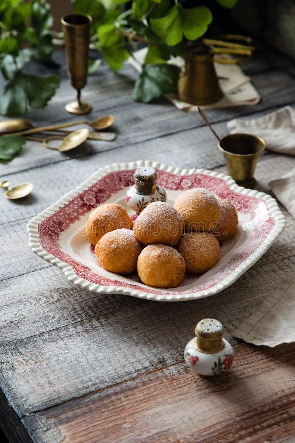 Homemade small round ball donuts sprinkled with powdered sugar on vintage plate. With pink ornament on grey wooden table with vintage powder shakers, towel stock image