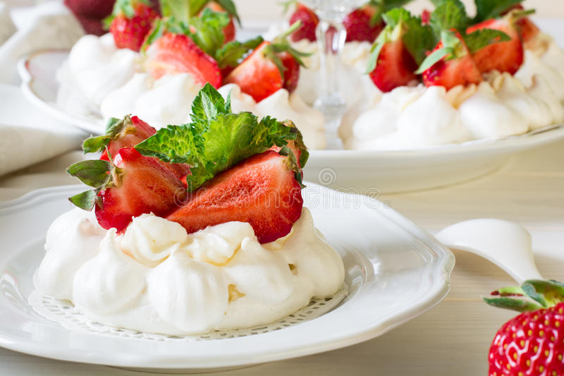 Homemade small strawberry pavlova meringue cakes with mascarpone cream and fresh mint leaves stock photo