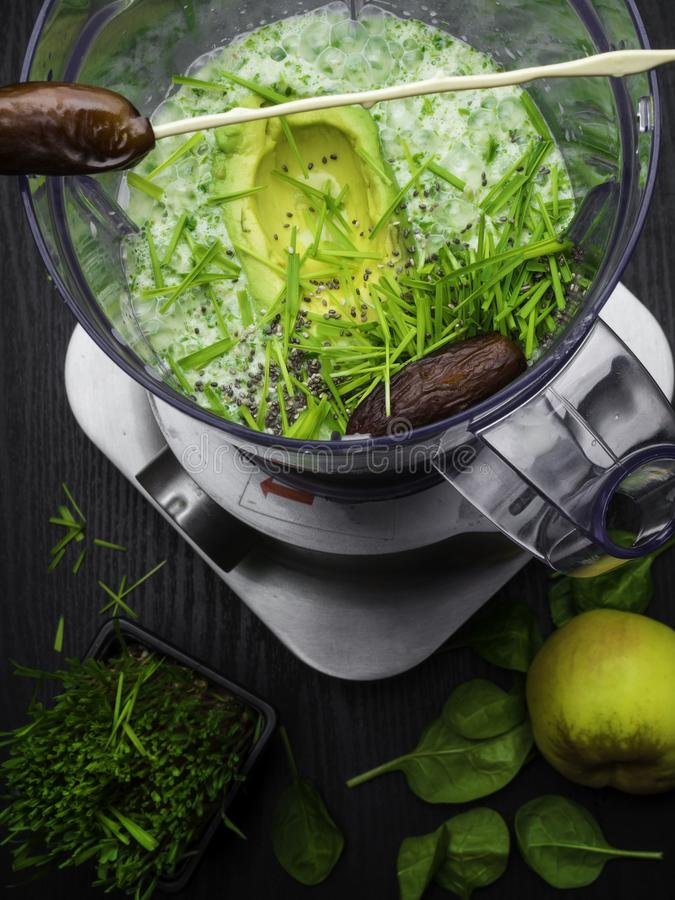 Green smoothie. Mixture of avocado, spinach, kiwi, banana, wheat grass, spirulina and coconut water. Homemade smoothie with fresh green fruits, wheat grass wheat stock photos