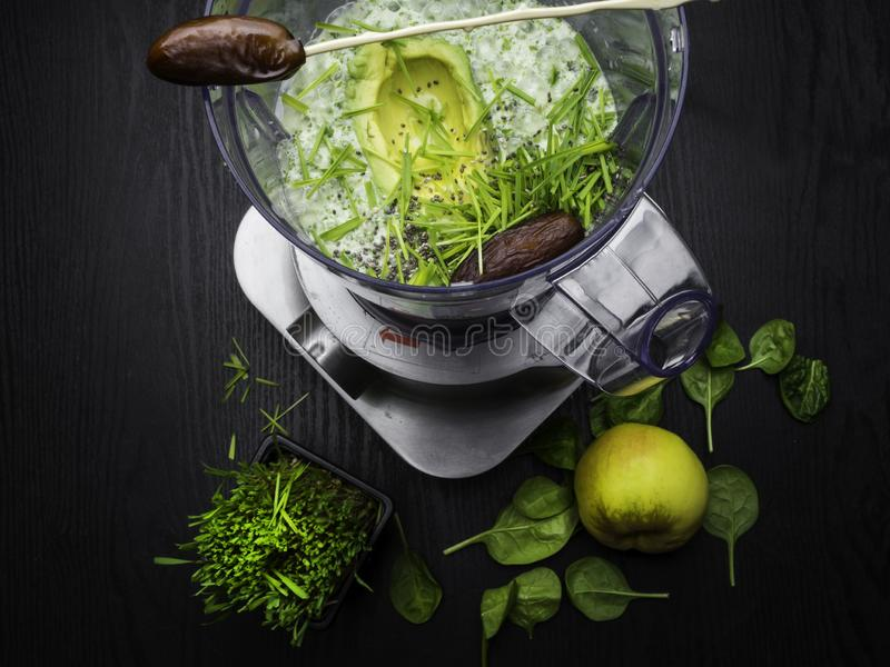 Homemade smoothie with fresh green fruits, wheat grass wheat grass, spinach, apple. Banana in blender royalty free stock image