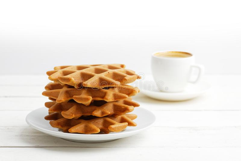 Homemade soft belgian waffles and cup of coffee on white wooden table royalty free stock image