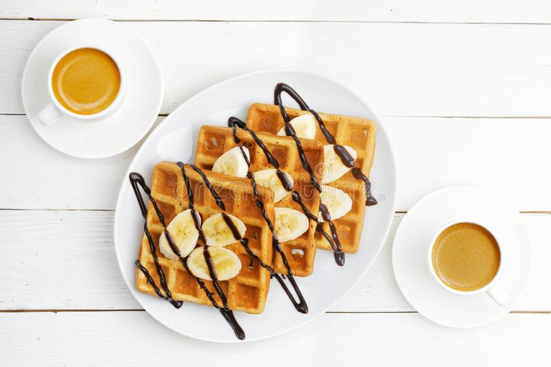 Homemade soft waffles with banana slices topped with chocolate and two cup of coffee on white wooden table royalty free stock photo