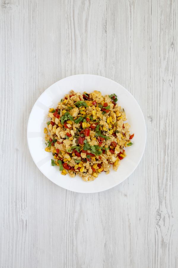 Homemade southwestern egg scramble on a white plate on a white wooden surface, top view. Flat lay, overhead, from above stock images