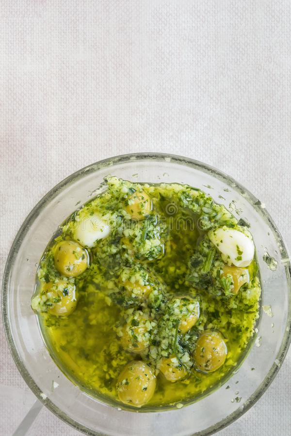 Homemade Spanish Style Pitted Green Olives Marinated in Oil with Garlic Herbs and Parsley. Top View. Mediterranean Cuisine royalty free stock photo