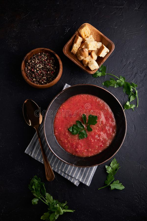 Homemade Spanish tomato soup Gazpacho with spice in black bowl on dark stone background royalty free stock images