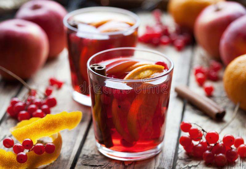 Homemade mulled wine or sangria with orange and apple slices, cranberries, cinnamon, anise on wooden table. Homemade spicy mulled wine or sangria autumn winter royalty free stock image