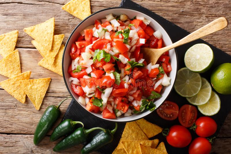 Homemade spicy pico de gallo close-up in a bowl and nachos. horizontal top view stock photography