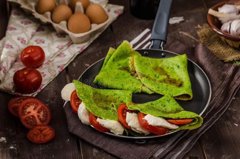 Homemade spinach crepes. Stuffed with basil, tomatoes and mozzarella stock image