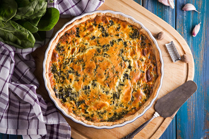Homemade spinach french pie quiche lorraine on wooden board top view royalty free stock photography