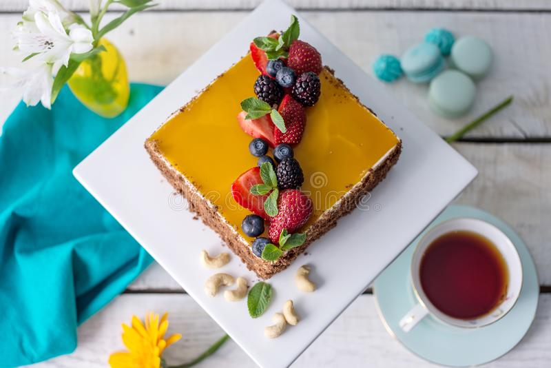Homemade square cake decorated on top of yellow jelly and berries with mint on light background. stock photography