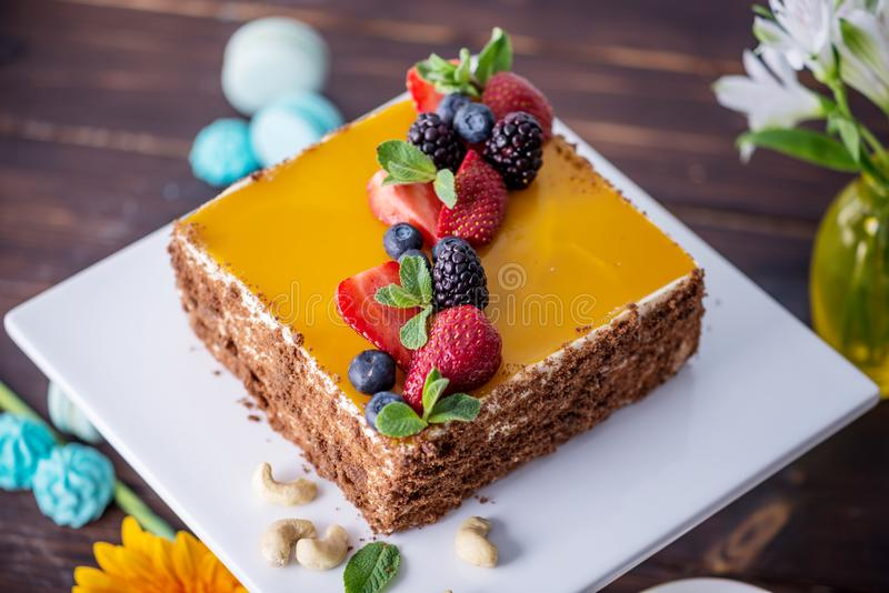 Homemade square cake decorated with yellow jelly on top and berries with mint on dark background royalty free stock photography