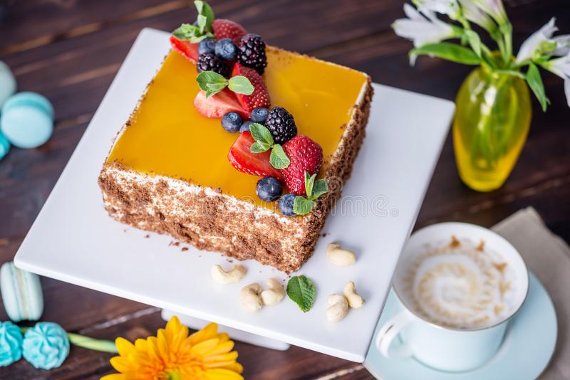 Homemade square cake decorated with yellow jelly on top and berries with mint on dark background stock images