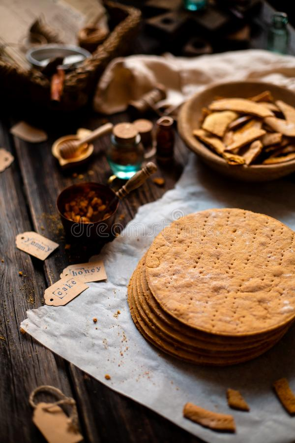 Homemade stack of baked layers of Russian traditional honey cake on baking paper on wooden rustic table stock image