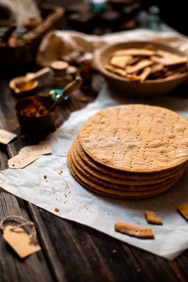 Homemade stack of baked layers of Russian traditional honey cake on baking paper on wooden rustic table royalty free stock images