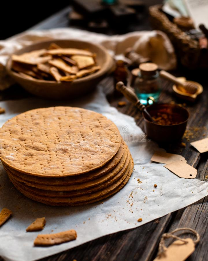 Homemade stack of baked layers of Russian traditional honey cake on baking paper on wooden rustic table stock photography