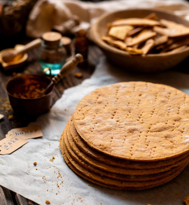 Homemade stack of baked layers of Russian traditional honey cake on baking paper on wooden rustic table royalty free stock photos