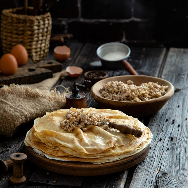 Homemade stack of crepes on wooden plate stand on rustic table with plate of ground fried beef royalty free stock photos