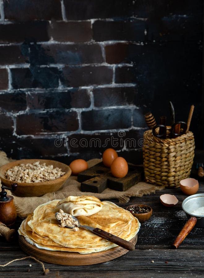 Homemade stack of crepes on wooden plate stand on rustic table with plate of ground fried beef stock images