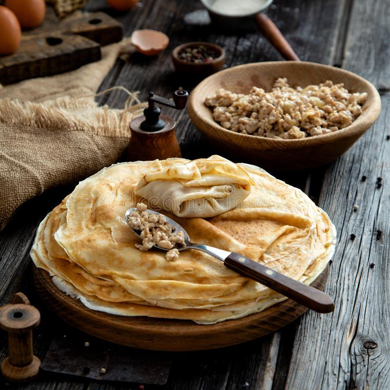 Homemade stack of crepes on wooden plate stand on rustic table with plate of ground fried beef. Homemade stack of crepes with spoon of ground fried meat on top royalty free stock photo