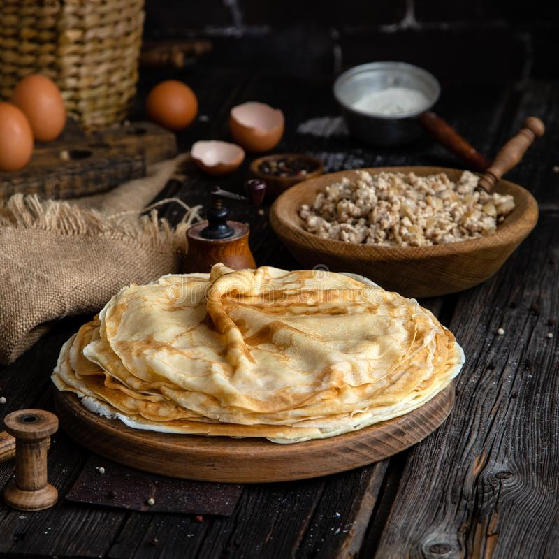 Homemade stack of crepes on wooden plate stand on rustic table with plate of ground fried meat, egg stand, eggs, sackcloth, strain. Er with flour, pepper, wicker stock image