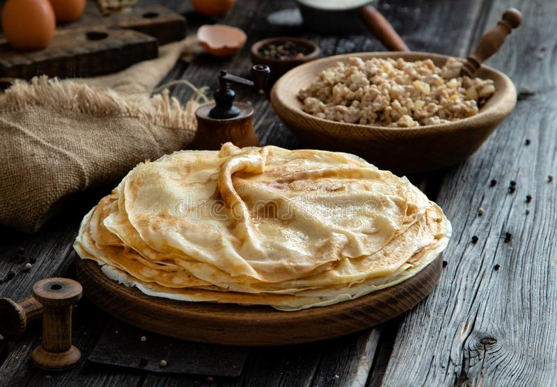 Homemade stack of crepes on wooden plate stand on rustic table with plate of ground fried beef royalty free stock image