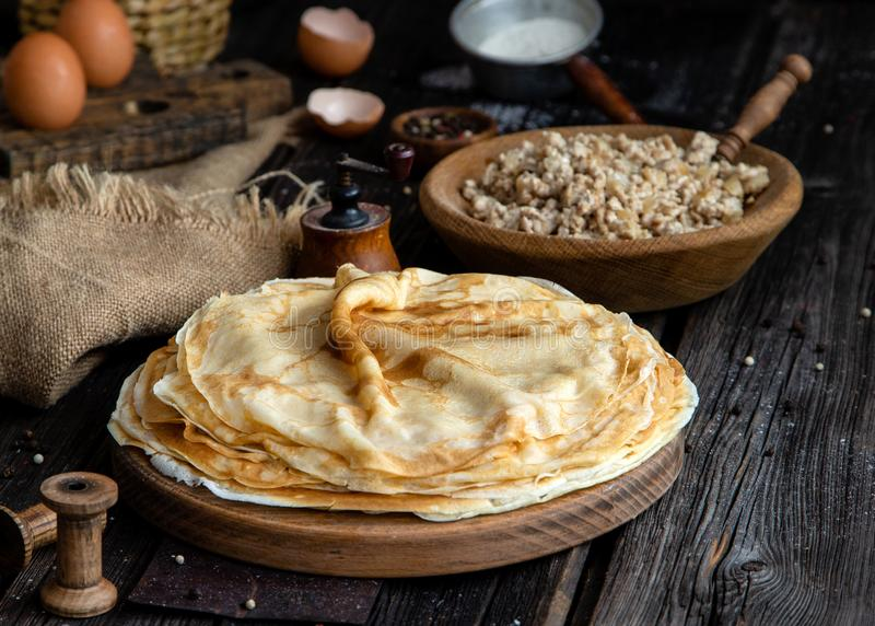 Homemade stack of crepes on wooden plate stand on rustic table with plate of ground fried beef. Homemade stack of crepes on wooden plate stand on rustic table royalty free stock photography