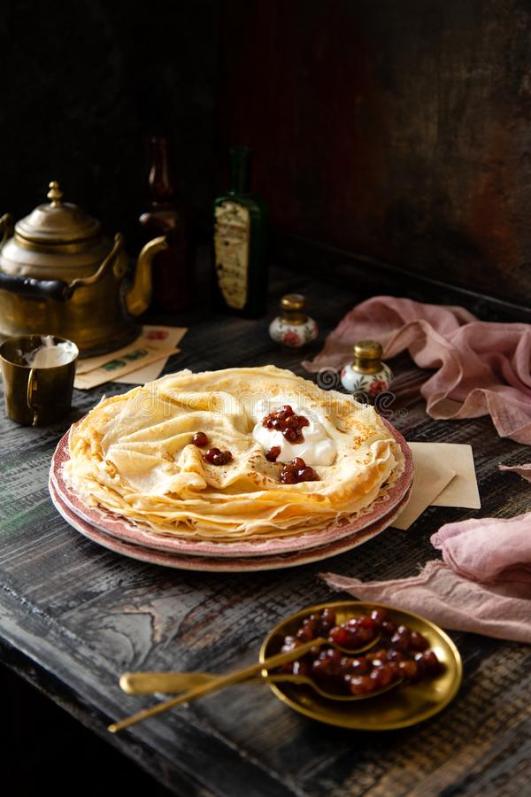 Homemade stack of thin crepes with sour cream and red jam on vintage pink plates. Stand on dark table with brass cup, teapot, spoons, saucer with jam, old stock image