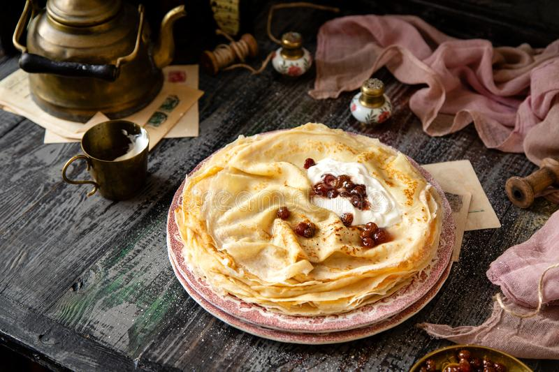 Homemade stack of thin crepes with sour cream and red jam on vintage pink plates. Stand on dark table with brass cup, teapot, spoons, saucer with jam, old royalty free stock image