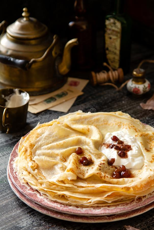 Homemade stack of thin crepes with sour cream and red jam on vintage pink plates. Stand on dark table with brass cup, teapot, spoons, old bottles, pink napkin royalty free stock photo