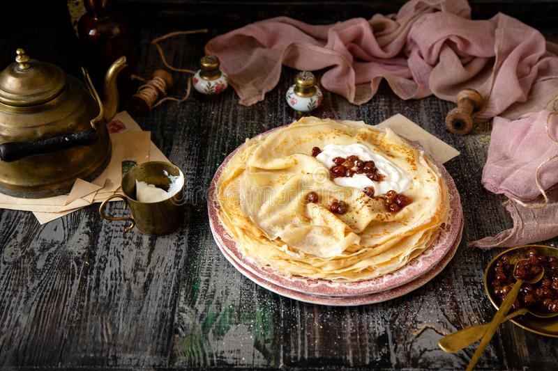 Homemade stack of thin crepes with sour cream and red jam on vintage pink plates royalty free stock image