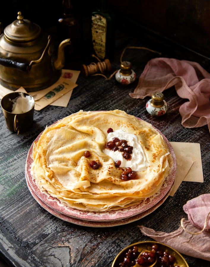 Homemade stack of thin crepes with sour cream and red jam on vintage pink plates. Stand on dark table with brass cup, teapot, spoons, saucer with jam, old stock photos