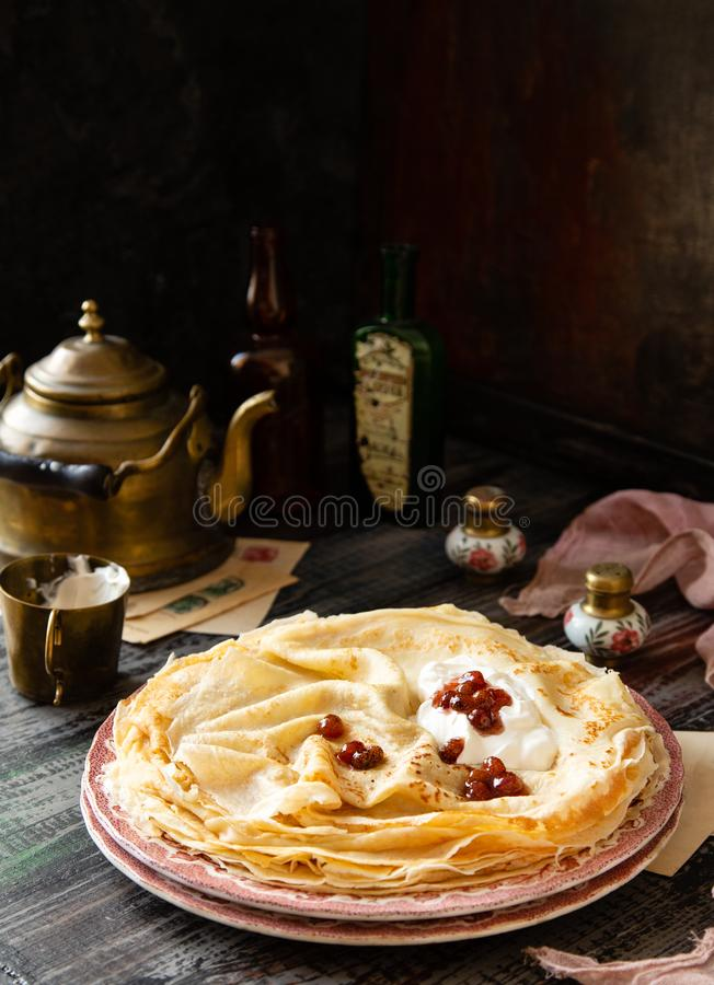 Homemade stack of thin crepes with sour cream and red jam on vintage pink plates. Stand on dark table with brass cup, teapot, spoons, saucer with jam, old stock images