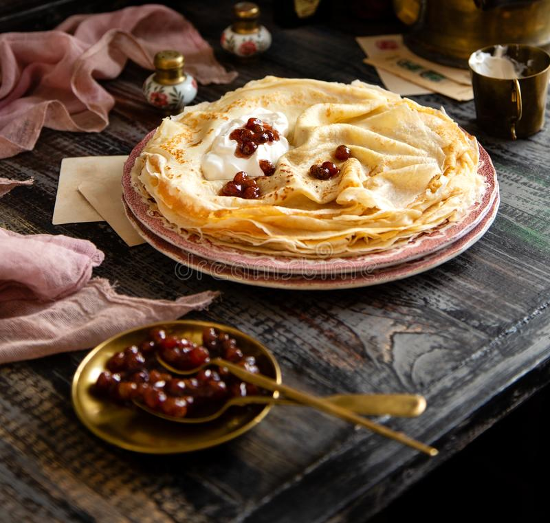 Homemade stack of thin crepes with sour cream and red jam on vintage pink plates stock image