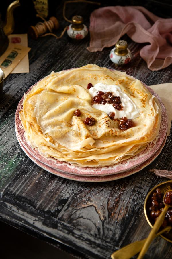 Homemade stack of thin crepes with sour cream and red jam on vintage pink plates stock images