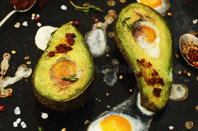 Homemade starter - baked avocado with quail egg and spices stock photo