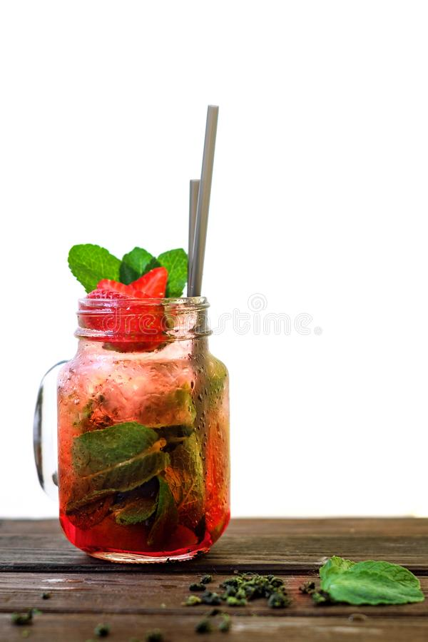Homemade strawberry iced tea in a jar on a wooden table. Cold home made strawberry iced tea in a jar on a wooden table and white background stock photo