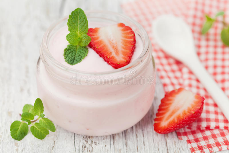 Homemade strawberry yoghurt decorated mint leaves in glass jar royalty free stock image