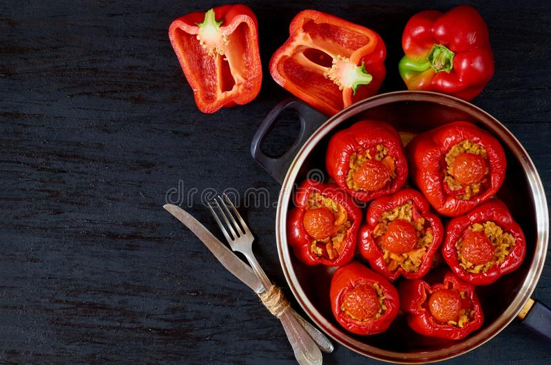 Homemade stuffed red bell peppers with rice and vegetables in a vintage frying pan on the black background. Top view stock images