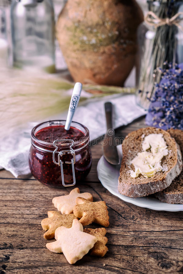 Homemade sugar honey cookies, raspberry jam in jar, bread and butter, knife, on a wooden background. Breakfast concept. stock images