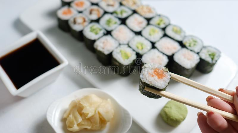Homemade sushi rolls japanese cuisine food. Homemade sushi assortment. Asian cuisine and Japanese food concept. Woman tasting rolls with chopsticks stock photo