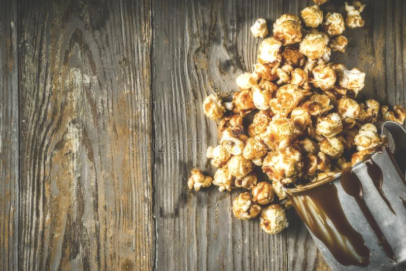 Homemade sweet caramel pop corn. With caramel topping, dark rustic background copy space royalty free stock photo