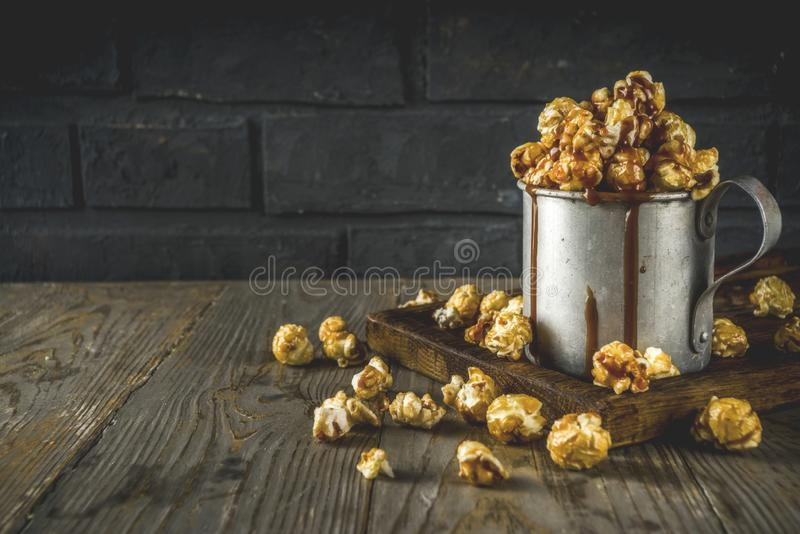 Homemade sweet caramel pop corn. With caramel topping, dark rustic background copy space stock photography