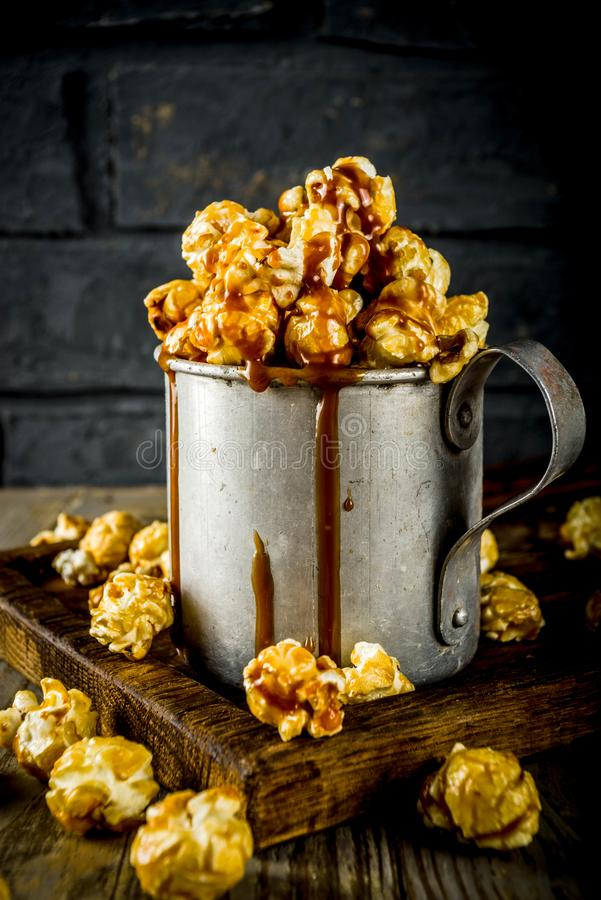 Homemade sweet caramel pop corn. With caramel topping, dark rustic background copy space stock images