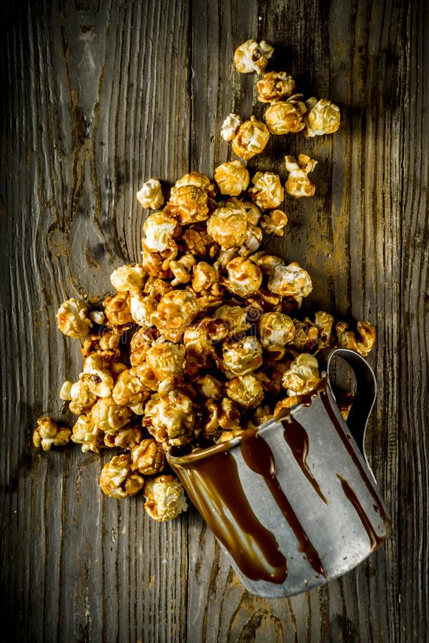 Homemade sweet caramel pop corn. With caramel topping, dark rustic background copy space stock image