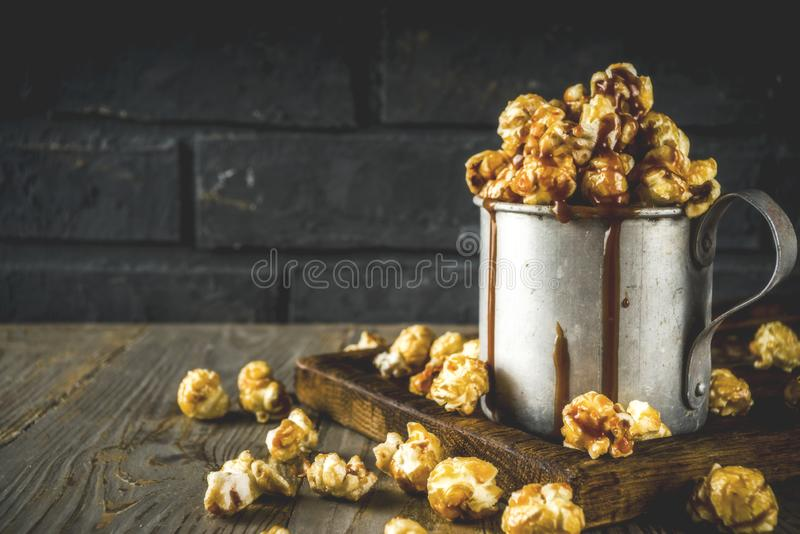 Homemade sweet caramel pop corn. With caramel topping, dark rustic background copy space royalty free stock images