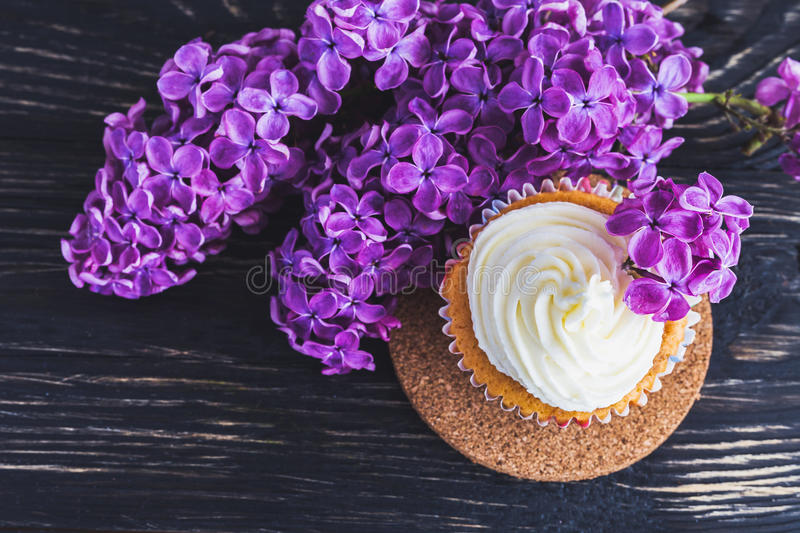 Homemade sweet cupcake with cream and flowers. Homemade tiramisu cupcakes with whipped cream and bouquet of purple lilac spring flowers on rustic wooden stock image