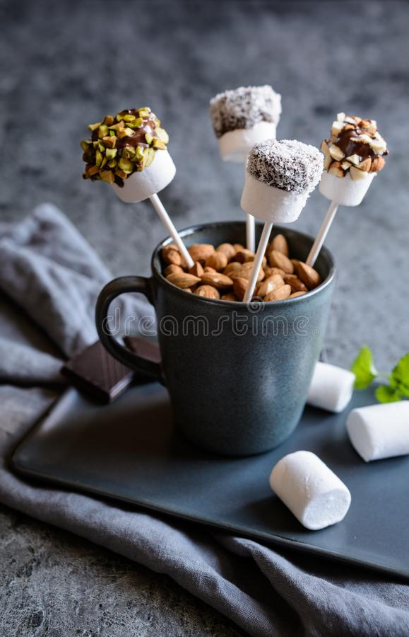 Sweet marshmallow pops with pistachios, almonds and grated coconut. Homemade sweet marshmallow pops dipped in chocolate, sprinkled with pistachios, almonds and royalty free stock photo